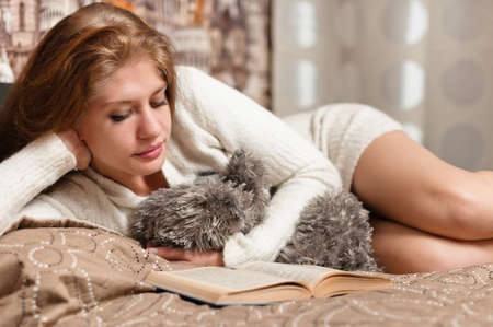 Pretty and cute woman reading a book while lying on bed photo