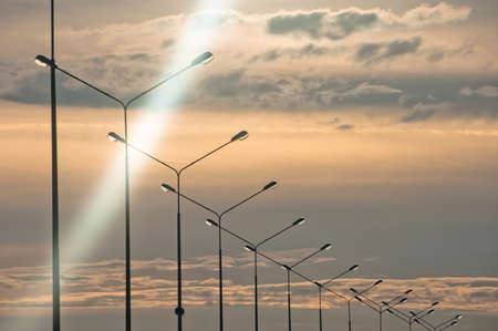 lamp post: Row of streetlights at evening time with cloudscape on background
