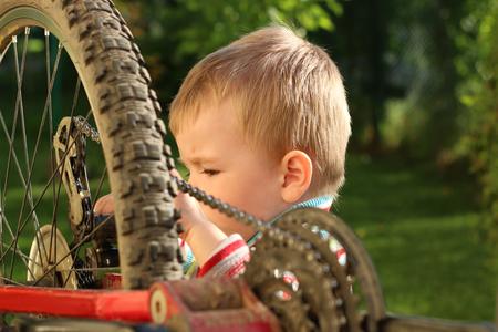 Little boy repairing bike adult