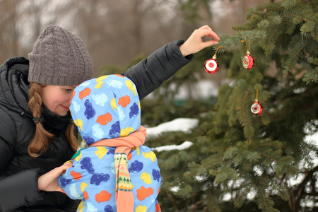 A mother and her child decorate the Christmas tree on the street in winter