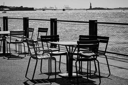 Black and white landscape. Chairs and desks on the pier. Imagens