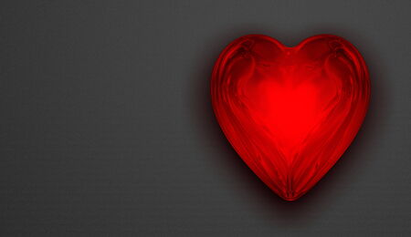 Red shiny reflective glass heart on grey textured background