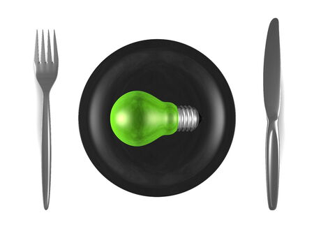 Green light bulb, black plate, steel fork and knife isolated on white background. Top view photo