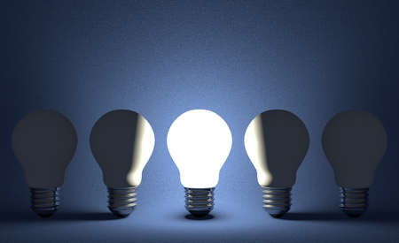 Glowing light bulb in row of switched off ones on dark blue textured background. Front view photo