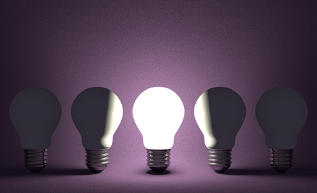 Glowing light bulb in row of switched off ones on dark violet textured background. Front view