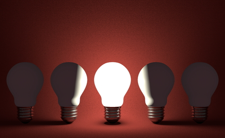 Glowing light bulb in row of switched off ones on dark red textured background. Front view photo
