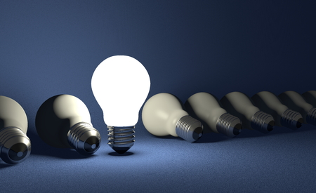 Standing glowing light bulb in row of lying switched off ones on dark blue textured background photo