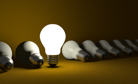 Standing glowing light bulb in row of lying switched off ones on dark yellow textured background photo