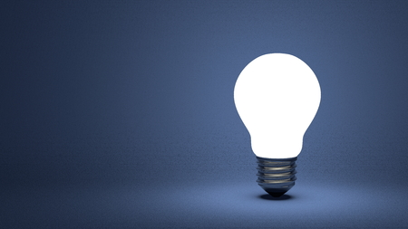 Glowing light bulb on dark blue textured background photo