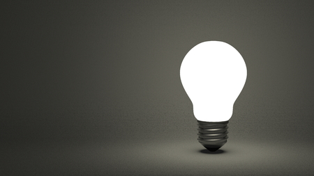 Glowing light bulb on dark gray textured background photo
