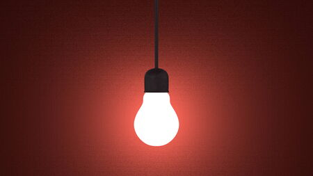 Glowing light bulb in lamp socket hanging on wire on dark red textured background photo