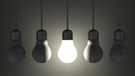 Glowing light bulb among dead ones in lamp sockets hanging on wires on dark gray textured background photo