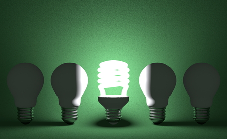 Glowing spiral light bulb in row of dead incandescent ones on dark green textured background. Front view photo