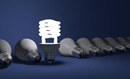 Standing glowing spiral light bulb in row of lying dead incandescent ones on dark blue textured background photo