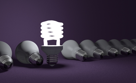 Standing glowing spiral light bulb in row of lying dead incandescent ones on dark violet textured background photo