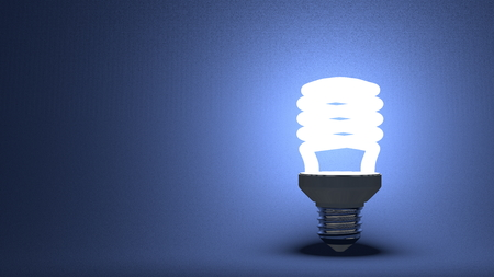 Glowing spiral light bulb on dark blue textured background photo