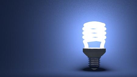 Glowing spiral light bulb on dark blue textured background photo
