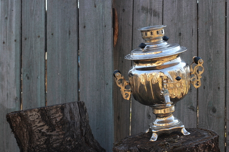 Old shiny samovar standing on stump on background of grungy wooden fence photo