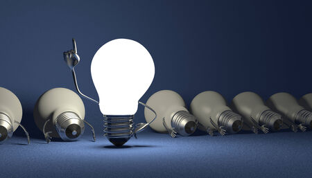 Glowing light bulb character in moment of insight standing among many switched off lying ones on blue textured background photo