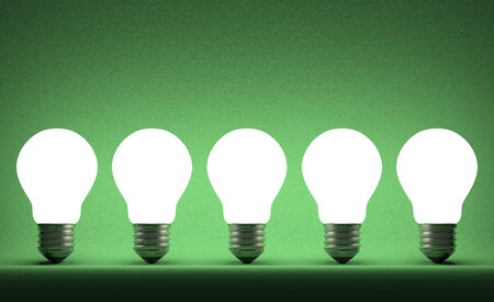 Row of glowing tungsten light bulbs on green textured background photo