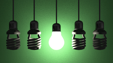 Glowing tungsten light bulb hanging among  switched off fluorescent ones in sockets on  wires on green textured background Imagens