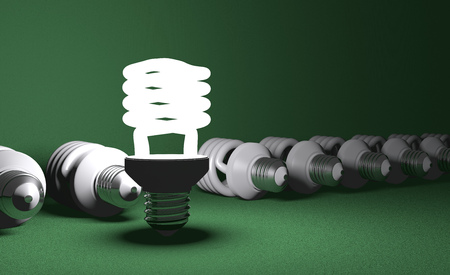 Glowing fluorescent light bulb standing in row of lying switched off ones on green textured background photo