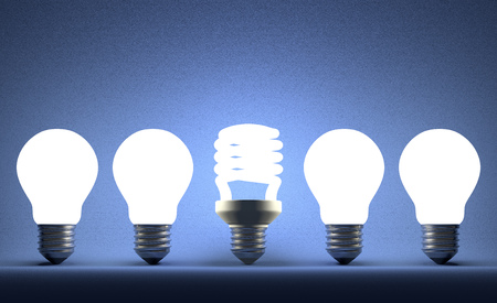 Glowing fluorescent light bulb in row of incandescent ones on blue textured background photo