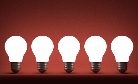 Row of glowing tungsten light bulbs on red textured background photo