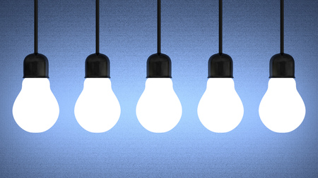 Row of hanging glowing tungsten light bulbs on blue textured background photo