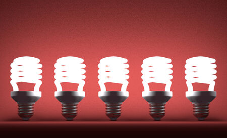 Row of glowing fluorescent light bulbs on red textured background photo
