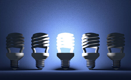 Glowing fluorescent light bulb among switched off ones on blue textured background photo
