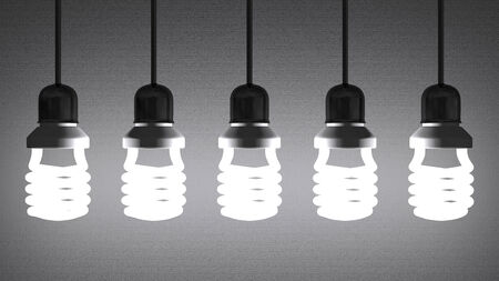 installed: Glowing fluorescent light bulbs installed in sockets hanging on wires on gray textured background Stock Photo