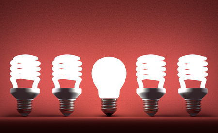 Glowing tungsten light bulb in row of fluorescent ones on red textured background photo