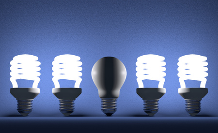 Switched off tungsten light bulb among glowing fluorescent ones on blue textured background photo