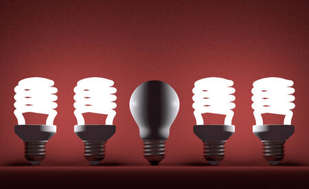 Switched off tungsten light bulb among glowing fluorescent ones on red textured background photo