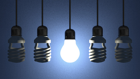 Glowing tungsten light bulb hanging among switched off fluorescent ones in sockets on wires on blue textured background photo