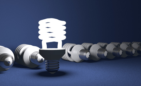 Glowing fluorescent light bulb standing in row of lying switched off ones on blue textured background photo