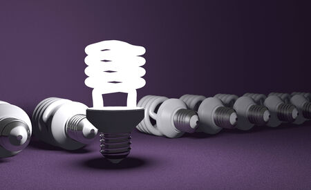Glowing fluorescent light bulb standing in row of lying switched off ones on violet textured background photo