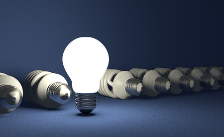 Glowing tungsten light bulb standing in row of lying switched off fluorescent ones on blue textured background photo