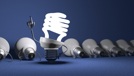 Glowing fluorescent light bulb character in moment of insight standing among many switched off lying tungsten ones on blue textured background photo