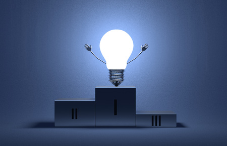 Glowing triumphant tungsten light bulb character on podium on blue textured background photo