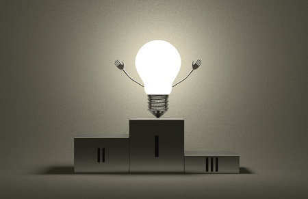 Glowing triumphant tungsten light bulb character on podium on gray textured background photo
