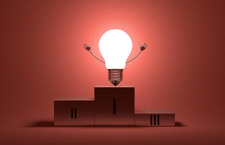 Glowing triumphant tungsten light bulb character on podium on red textured background photo