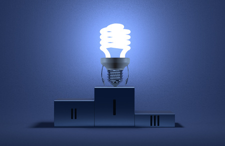 Glowing fluorescent tungsten light bulb character on podium on blue textured background photo