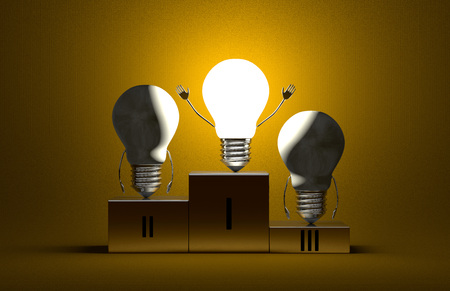 Triumphant glowing tungsten light bulb character and two switched off ones on podium on yellow textured background photo