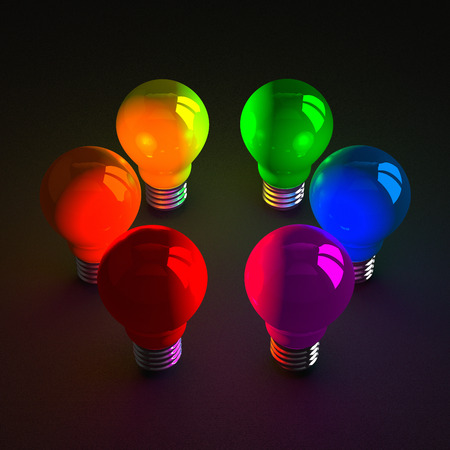 Glowing light bulbs of various colors standing on dark textured background photo