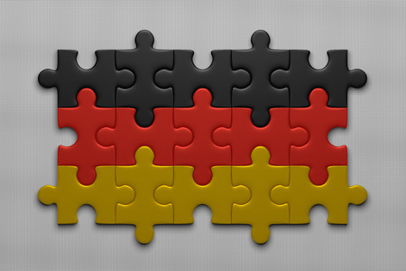 assembled: German flag assembled of puzzle pieces on gray background