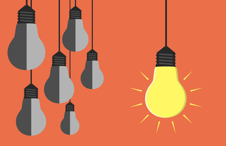 One glowing light bulb hanging beside many gray dull ones. Innovation, motivation, insight, inspiration concept.