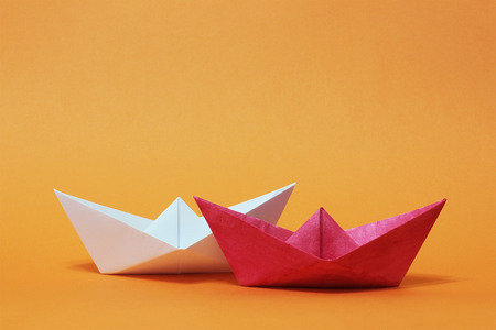 Competition between two paper boats. Red and white ships sailing on orange background. Rivalry, business, success and efficiency concept Stock Photo