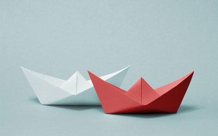 run faster: Two paper boats competing with each other. Red and white ships sailing on gray background. Rivalry, business, success and efficiency concept